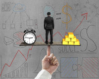 Businessman between clock and gold balance on seesaw Stock Photos