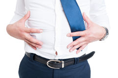 Businessman in closeup holds his stomach because of bloating Royalty Free Stock Image