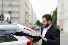 Businessman closing the boot of his car Royalty Free Stock Photography