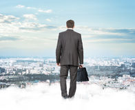 Businessman on clouds looking at city Stock Images