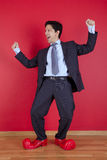Businessman with clown shoes. Happy businessman next to a red wall with clown shoes Stock Photos