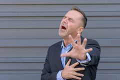 Businessman clutching his chest in pain. Or anguish while reaching out with his other hand in desperation against a grey wall with copy space stock images