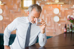 Businessman clutching whiskey glass to forehead Royalty Free Stock Photo