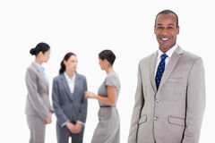 Businessman with co-workers talking. Close-up of a businessman smiling with three female co-workers talking seriously in the background Stock Image