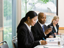 Businessman with co-workers text messaging on cell Stock Images