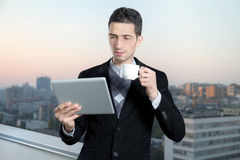 Businessman On Coffee Break. Businessman with a cup of coffee uses a digital tablet on the roof of business center Royalty Free Stock Photos