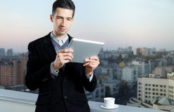 Businessman On Coffee Break. Businessman with a cup of coffee uses a digital tablet on the roof of business center Stock Image