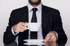 Businessman and a coffee cup. Businessman holding a cup of coffee Stock Photo