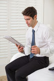 Businessman with coffee cup and newspaper at a hotel room Royalty Free Stock Images