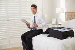 Businessman with coffee cup and newspaper by luggage at hotel room Stock Photography