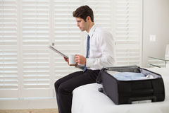 Businessman with coffee cup and newspaper by luggage at hotel room Stock Images