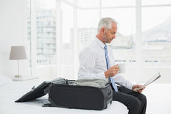 Businessman with coffee cup reading newspaper by luggage at hotel room Royalty Free Stock Photo