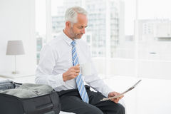 Businessman with coffee cup reading newspaper by luggage Royalty Free Stock Photography