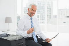 Businessman with coffee cup reading newspaper by luggage Stock Photos