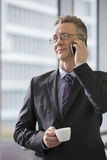 Businessman with coffee cup using cell phone in office Stock Photos