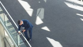 Businessman with coffee cup using mobile phone in office building. High angle view of middle-aged Caucasian businessman with coffee cup using mobile phone in royalty free stock images