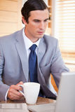 Businessman with coffee on his laptop Stock Photography