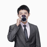 Businessman with coffee mug, studio shot Royalty Free Stock Images