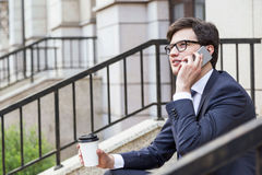 Businessman with coffee on phone Royalty Free Stock Photography