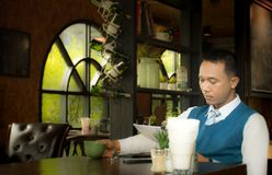 Businessman in a coffee shop reading a contract document. Royalty Free Stock Photos
