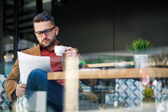 Businessman in a coffee shop reading a contract document. Outdoo Stock Photography