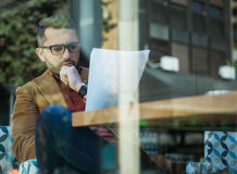 Businessman in a coffee shop reading a contract document. Outdoo Royalty Free Stock Image