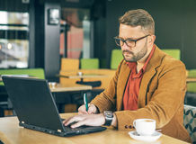 Businessman in coffee shop work on his laptop. Outdoor portrait Stock Images