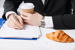 Businessman with coffee writing something Stock Images