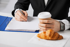Businessman with coffee writing something Stock Photo