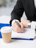 Businessman with coffee writing something Stock Photography