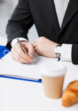 Businessman with coffee writing something Stock Image