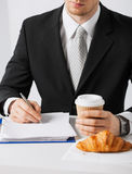 Businessman with coffee writing something Royalty Free Stock Image