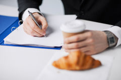 Businessman with coffee writing something Royalty Free Stock Photography