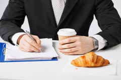 Businessman with coffee writing something Royalty Free Stock Photos
