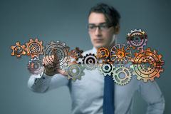 The businessman with cogwheels gear in teamwork concept Royalty Free Stock Photo