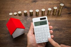 Businessman With Coins And House Model Using Calculator Royalty Free Stock Photography