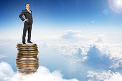 Businessman on coins pile in sky Royalty Free Stock Photography