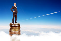 Businessman on coins pile in sky Stock Photo