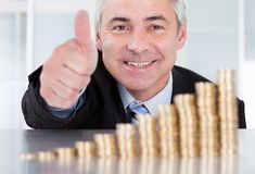 Businessman with coins showing thumbs up sign Stock Images