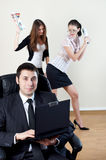 Businessman with collaborator on backside. Businessman with laptop sit in an armchair with collgues on backside royalty free stock photography