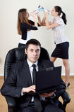 Businessman with collaborator on backside. Businessman with laptop sit in an armchair with collgues on backside royalty free stock photo