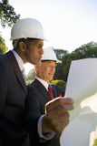 Businessman and colleague in hardhats looking at blueprint, low angle view Royalty Free Stock Photography