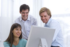 Businessman and colleague looking at woman's monitor, smiling Royalty Free Stock Photos