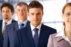 Businessman With Colleagues. Young serious businessman standing in the row with his colleagues Royalty Free Stock Photo