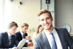 Businessman with colleagues in the background in office. Royalty Free Stock Images