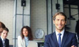 Businessman with colleagues in the background in office. Royalty Free Stock Photos