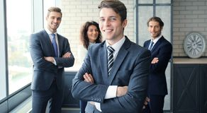 Businessman with colleagues in the background in office. Stock Photos