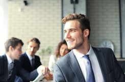 Businessman with colleagues in the background in office. Royalty Free Stock Photo