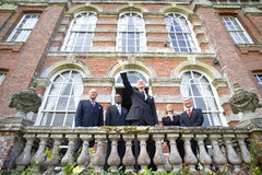 Businessman by colleagues on balcony of manor house with arm raised, low angle view Stock Photography