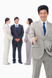 Businessman with colleagues behind him extending his hand Royalty Free Stock Photo